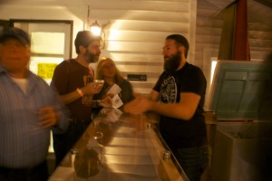 Lain (right) chats with the owners of Gibb's Hundred Brewing in Greensboro.