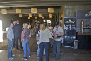 People mingle near tables for service and supplies providers at the conference.